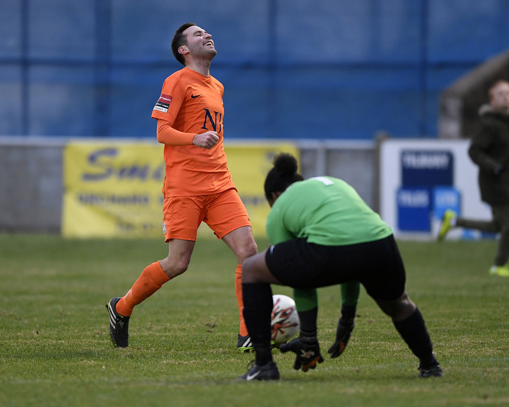 footballer smiles as he misses a chance