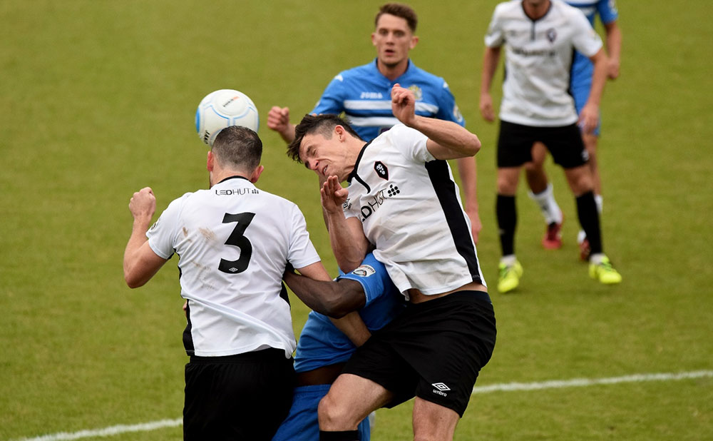 two footballers challenge for a header