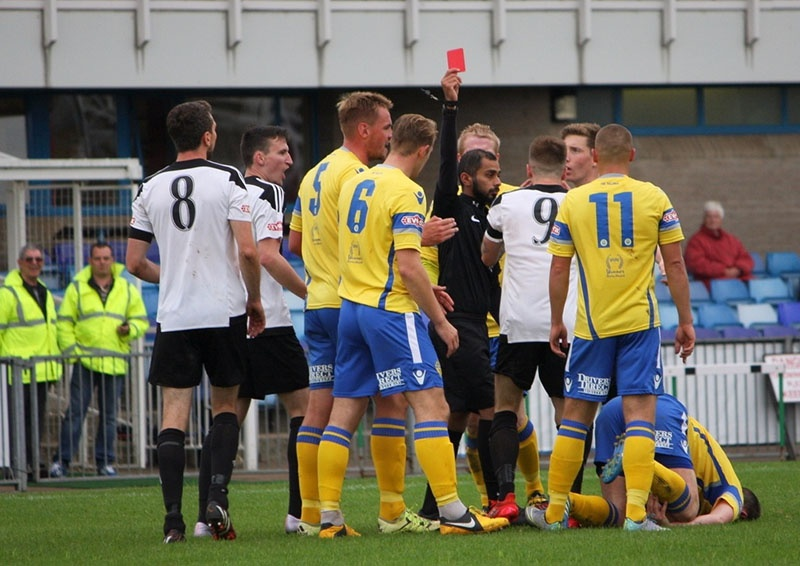 football referee issues red card to player