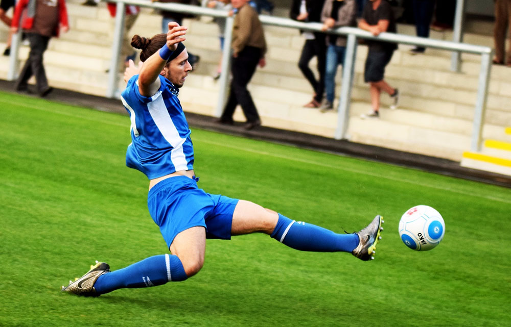 football player stretches for the ball