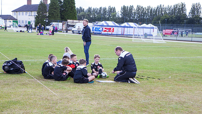 youth coach shares tactics-with-team
